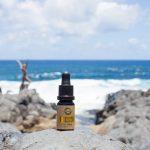 CBD-olie på Hawaii med hav og kvinde i baggrunden